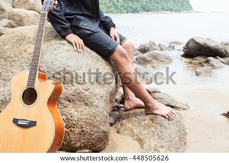 Handsome romantic guitarist play music siting on beach rock. - stock photo