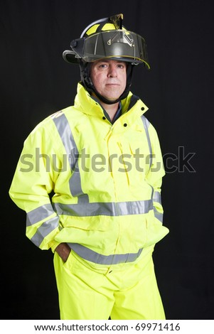 Handsome, rugged firefighter photographed on a black background. - stock photo
