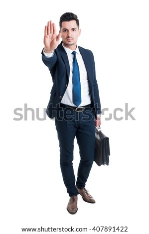 Handsome sales man showing stop gesture standing and holding a briefcase isolated on white background - stock photo