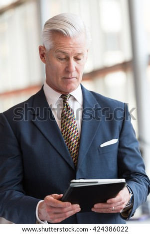 handsome senior business man with grey hair working on tablet computer at modern bright office interior - stock photo
