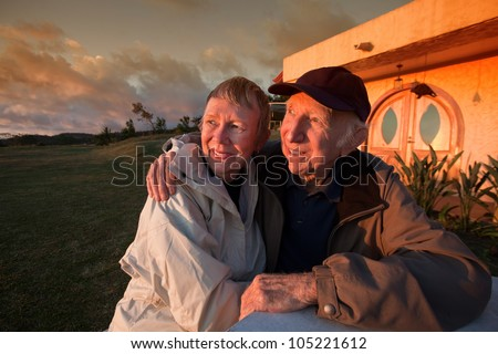 Handsome senior couple looking toward a sunset outside - stock photo