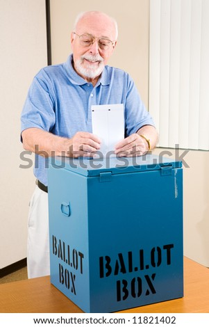 Handsome senior man casting his ballot at the polls. - stock photo