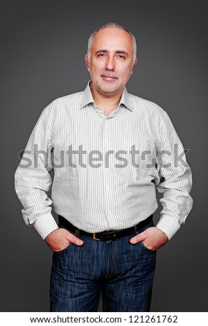 handsome senior man looking at camera and smiling. studio shot over grey background - stock photo