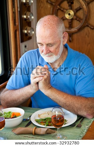 Handsome senior man saying grace over a meal in his motor home. - stock photo