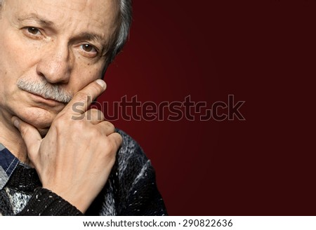 Handsome senior man with a skeptical expression on dark red background with copy-space - stock photo