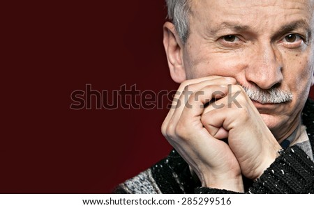 Handsome senior man with a skeptical expression on red background with copy-space - stock photo