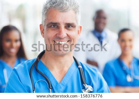 handsome senior medical surgeon portrait in hospital - stock photo