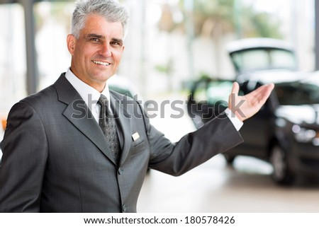 handsome senior vehicle salesman presenting new cars at showroom