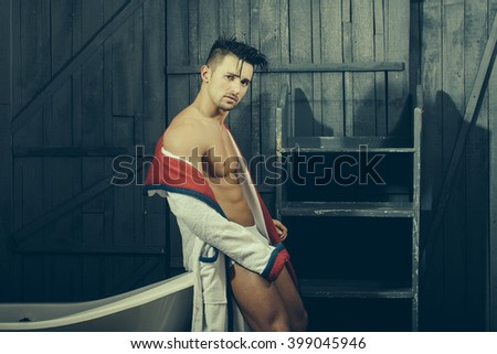 Handsome sensual sexy young man in white panties and terry bathrobe with bare muscular torso and beautiful body indoor near bathtub in bath room, horizontal picture - stock photo