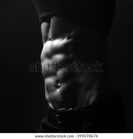 Handsome sensual sexy young stylish thoughtful man in black shirt with fashionable hairdo undressing with bare muscular torso and beautiful body indoor on studio background, square picture - stock photo