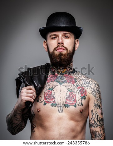Handsome serious man with tattooed body - stock photo