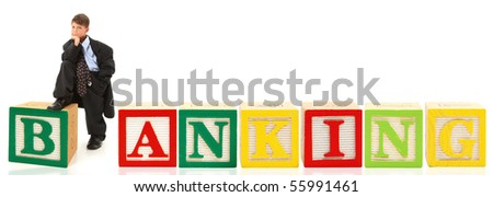 Handsome seven year old american boy in over sized suit with the word banking in giant alphabet blocks. - stock photo