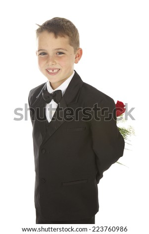 Handsome seven year old boy on a white background with a missing front tooth.  He is wearing a black suit with a bow tie and holding a long stemmed red rose