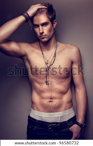 Handsome sexy bare chested man wearing a cross around his neck and posing showing off his muscles with his hand to his head. - stock photo