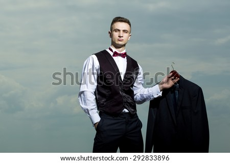 Handsome sexy brutal strong muscular man in formal suit with bow tie holding jacket standing on blue sky background copyspace, horizontal picture - stock photo