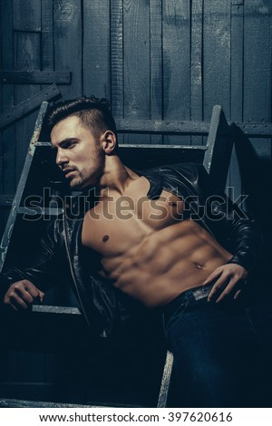 Handsome sexy muscular stylish young man in leather jacket with bare torso sitting indoor near stairs on wooden background, vertical picture - stock photo