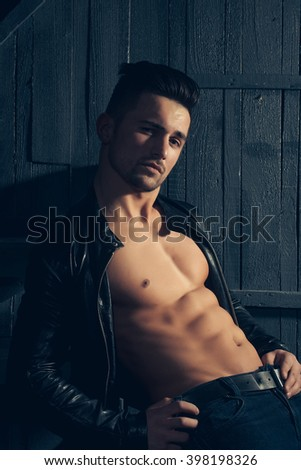Handsome sexy sensual muscular stylish young man in leather jacket with bare torso sitting indoor on wooden background, vertical picture - stock photo