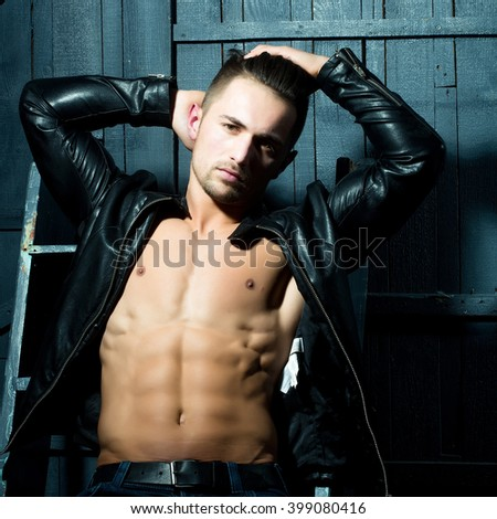 Handsome sexy sensual muscular stylish young man in leather jacket with bare torso sitting indoor near stairs on wooden background, square picture - stock photo