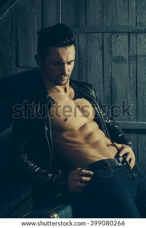 Handsome sexy sensual muscular stylish young man in leather jacket with bare torso sitting on retro suit case indoor on wooden background, vertical picture