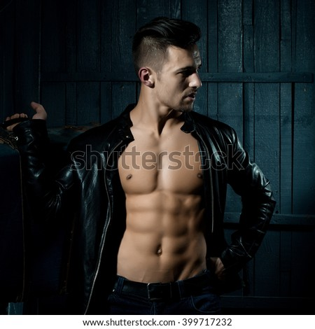 Handsome sexy sensual muscular stylish young man in leather jacket with bare torso standing with retro suit case near stairs indoor on wooden background, square picture - stock photo