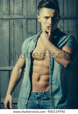 Handsome sexy sensual muscular young macho man with bare torso and stylish hair in jeans shirt indoor on wooden background, vertical picture - stock photo