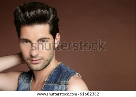 Handsome sexy young man portrait denim jacket brown background