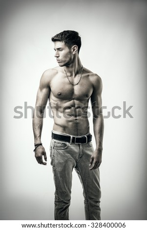 Handsome shirtless athletic young man in jeans, looking to a side in studio shot,  on white background - stock photo