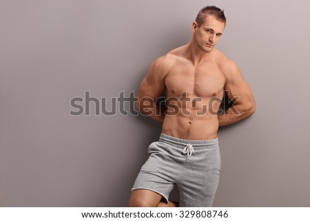 Handsome shirtless man leaning against a gray wall and looking at the camera - stock photo