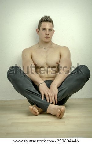 Handsome shirtless muscular man with elegant pants, sitting, studio shot on light background - stock photo