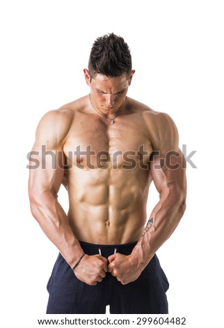 Handsome shirtless muscular man with elegant pants, standing, studio shot isolated on white background - stock photo