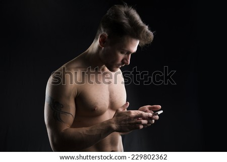 Handsome shirtless muscular young man using cell phone on dark background - stock photo