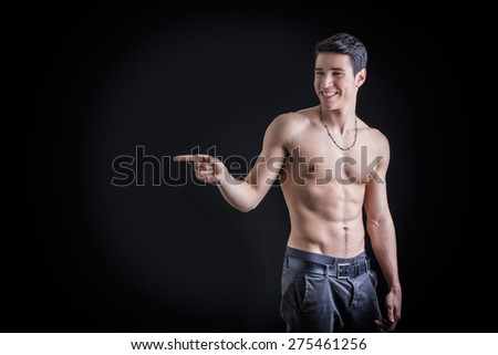 Handsome shirtless young man laughing and pointing finger to a side, on black background - stock photo