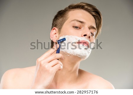 Handsome shirtless young man shaving his face while standing on grey background.