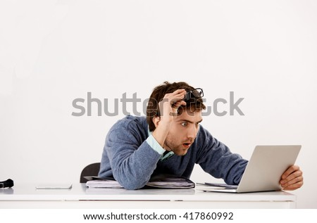 Handsome shocked young businessman in glasses sitting at the office desk staring at screen of his laptop. Isolated on white background. - stock photo