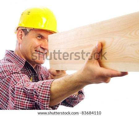 handsome skilful carpenter measures the board isolated on white background - stock photo