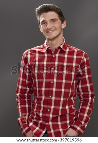 handsome smile - portrait of a friendly young male student with hands in pockets looking serious and happy, grey background studio - stock photo