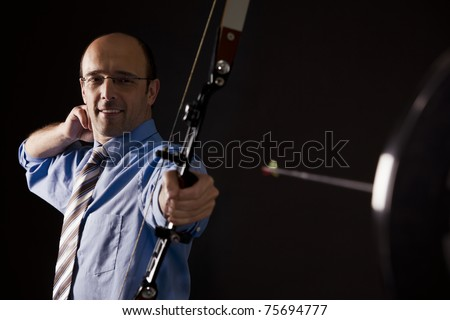 Handsome smiling businessman in blue short and tie hitting the target with bow and arrow, isolated on black background.