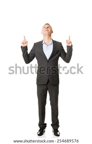 Handsome smiling businessman pointing upwards.  - stock photo