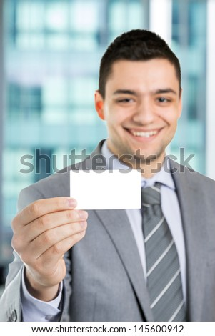 Handsome smiling businessman showing his business card.