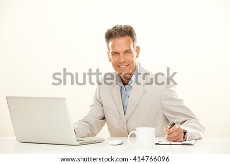 handsome smiling businessman work with laptop isolated on white