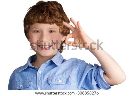 Handsome smiling caucasian boy with red hair showing OK sign with his hand. Isolated on white background - stock photo