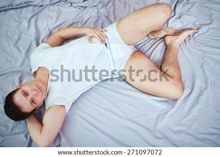 Handsome smiling caucasian young man in white t-shirt and underwear lying or sitting on a bed. Isolated over gray sheet. Domestic atmosphere photo. Sexy attractive male lover in bedroom. Top view - stock photo