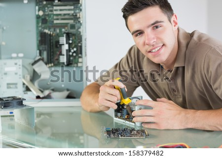 Handsome smiling computer engineer repairing hardware with pliers in bright office - stock photo