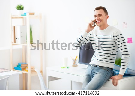 Handsome smiling guy talking on cell phone  - stock photo
