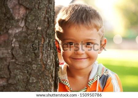 Handsome smiling little boy near a tree in the sunset light. Close-up portrait. - stock photo
