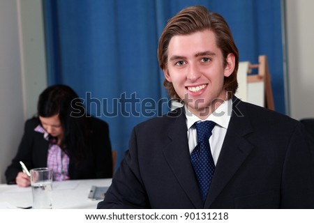 Handsome smiling male executive in business meeting - stock photo