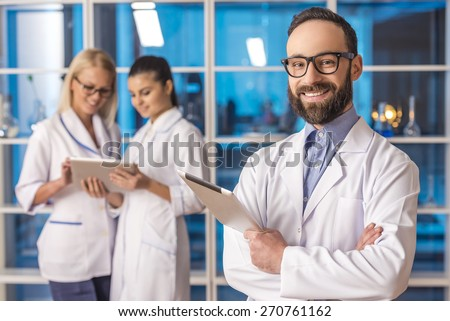 Handsome smiling male scientist with tablet looking at camera on the background his colleague at the laboratory. - stock photo