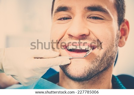 Handsome smiling man at doing checkup at dentist's surgery  - stock photo