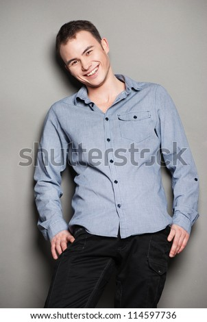 Handsome smiling man casually leaning against the wall - stock photo