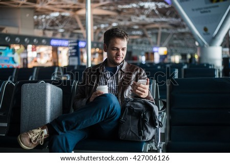 Handsome smiling man in casual wear holding luggage and messaging through his mobile phone while sitting at the hall of airport with coffee cup - stock photo